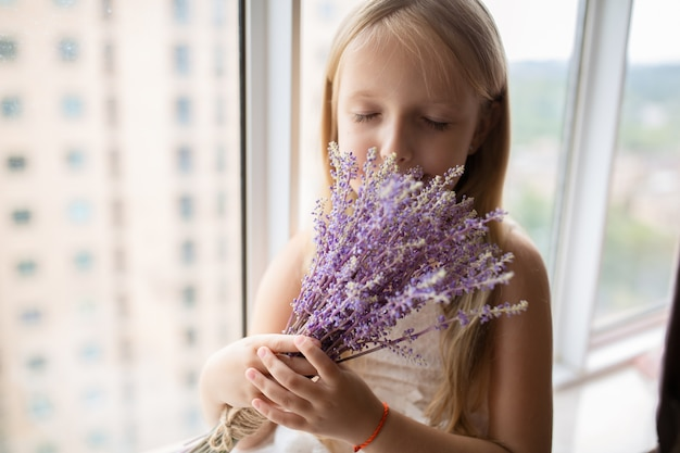 Girl with blonde hair holding bouquet of purple flowers