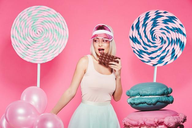 분홍색에 거대한 달콤한 막대 사탕으로 서있는 상단과 치마를 입고 금발 머리를 가진 소녀