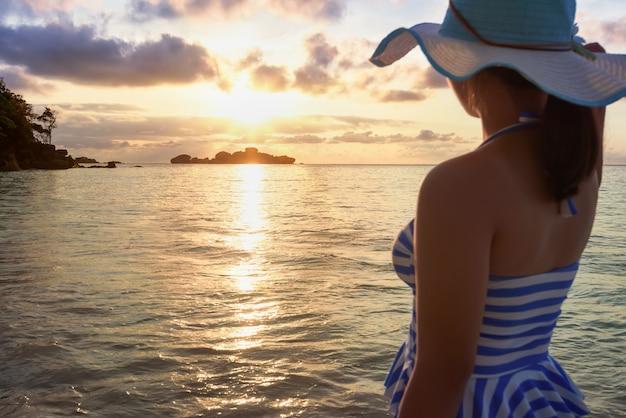 青と白の縞模様の水着が立っている女の子は、タイ、パンガー、シミラン諸島国立公園、ミアン島のハネムーンベイのビーチで日の出中に自然の空と海を眺めます