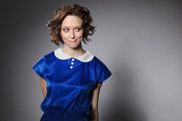 파란 드레스와 생강 물결 모양의 머리와 검은 격리 된 배경에 메이크업 소녀.