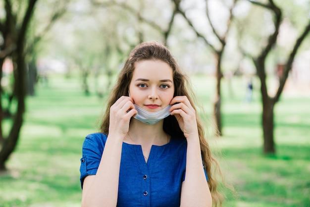 Девушка с голубыми глазами в маске в цветущем парке.