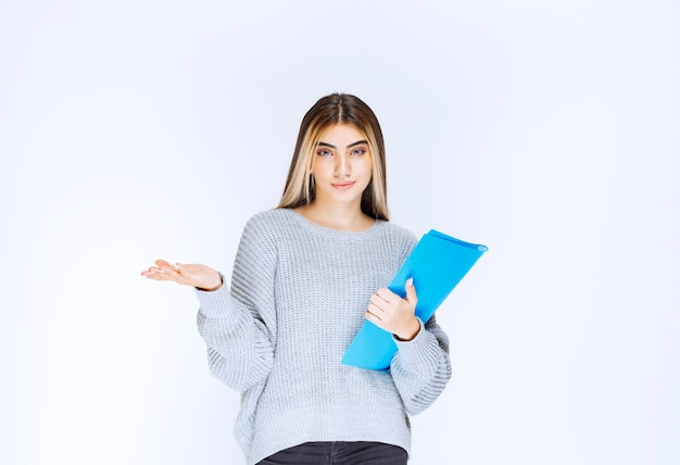 La ragazza con una cartella blu ha completato le attività in tempo e si sente fresca.