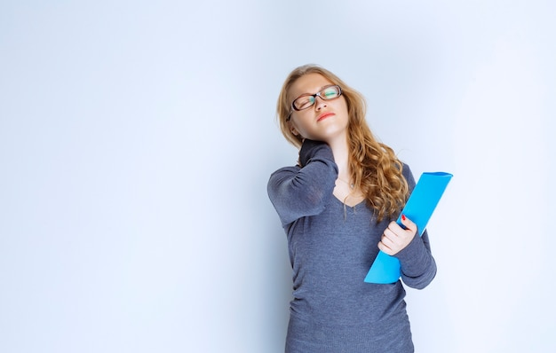 La ragazza con una cartella blu sembra assonnata e stanca.
