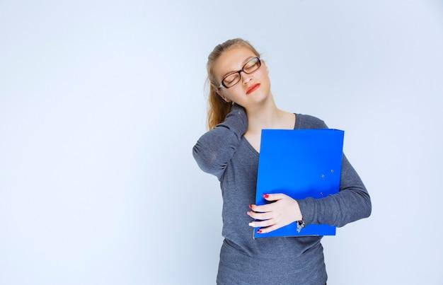 青いフォルダーを持つ女の子は疲れているように見えます。
