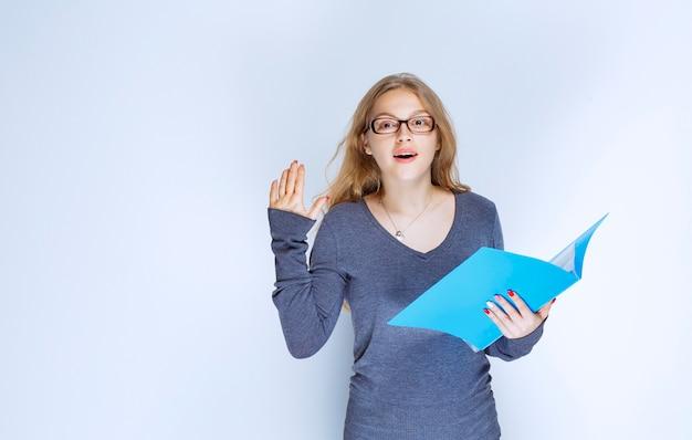 Ragazza con una cartella blu che alza la mano per attirare l'attenzione.
