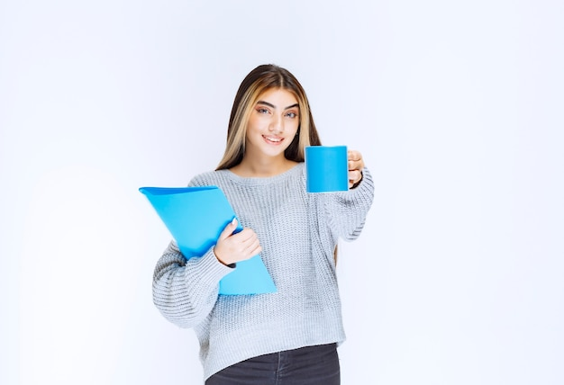 Ragazza con una cartella blu che condivide una tazza di caffè con il suo collega.