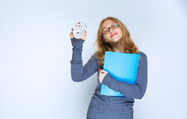 Girl with a blue folder showing her alarm clock.