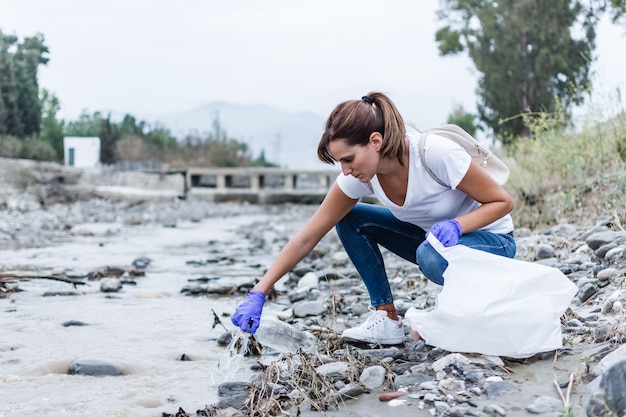 Girl with blue gloves crouched on the bank of the river taking plastic out of the water to recycle