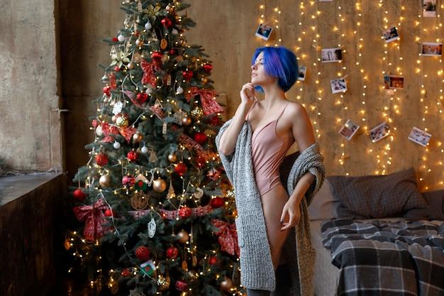 집에서 크리스마스 트리에서 파란 머리를 가진 여자