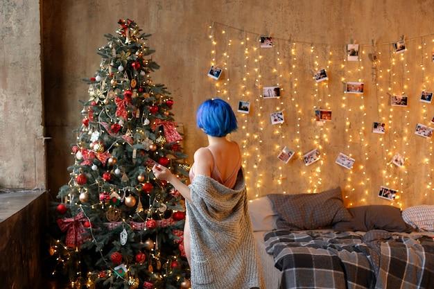 크리스마스 나무에 파란 머리를 가진 소녀입니다. 뒤에서보기