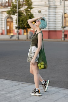 Girl with blue hair and string bag walks in the evening in the city