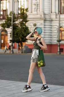 A girl with blue hair walks around the city with a green bag of fruit. bright summer