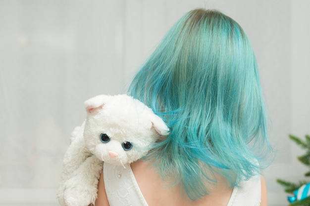 Girl with blue hair in a white dress and a toy cat
