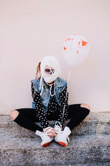 Girl with bondaged face and blood balloon