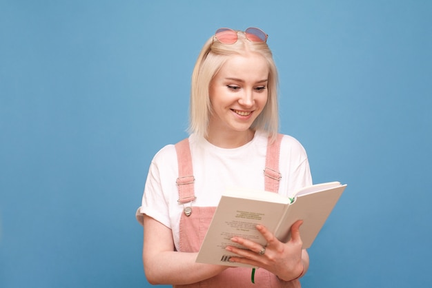Girl with a book in her hands on blue smiles and reads