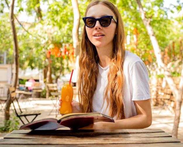 フレッシュジュースのボトルを保持している本を持つ少女