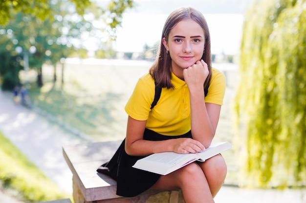 Девушка с книгой, глядя на камеру