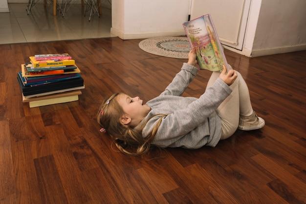 Girl with book lying on floor