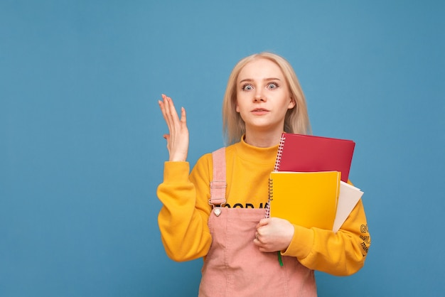 Girl with books and notebooks in her hands stands on blue and looks unhappy in the camera