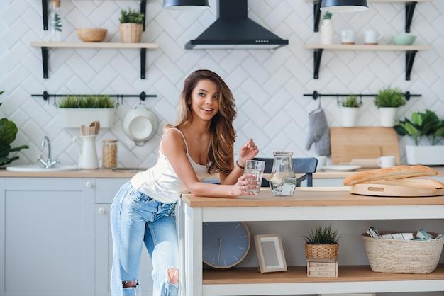 Девушка с бутылкой воды и стакан на кухне
