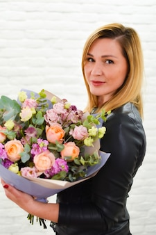 Girl with a bouquet of colorful flowers in a flower shop.