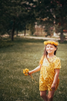 A girl with a bouquet of dandelions and a wreath of yellow dandelions on her head is waiting for bir...
