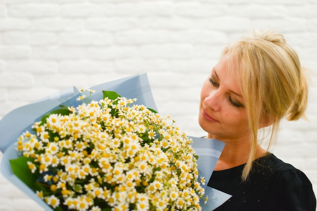 Girl with a bouquet of delicate daisies.