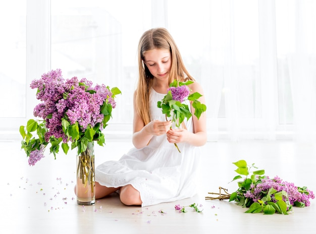 Girl with bouquet of lilac flowers sitting on the floor