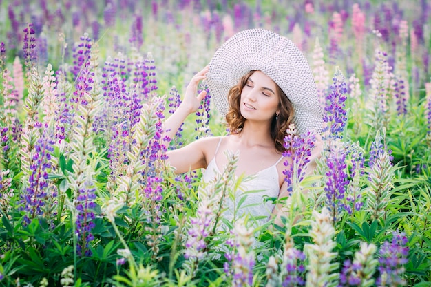 Girl with a bouquet of lupine on the field