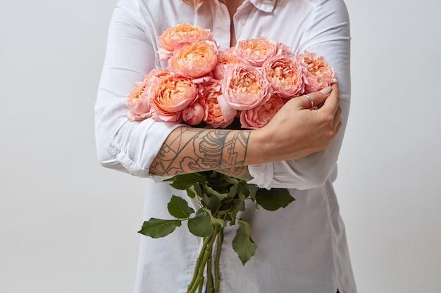 花の花束を手にした女の子。ピンクのバラの花束、バレンタインデー
