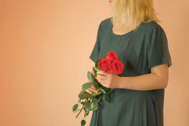 Девушка с букетом красных роз. весенний букет красных роз в руках женщины
