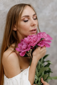 Girl with a bouquet of peonies on a gray background close-up