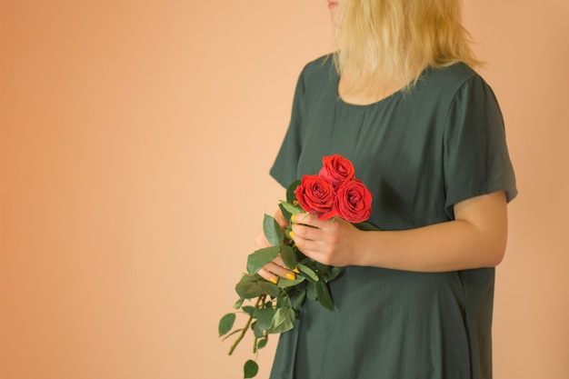 Girl with bouquet of red roses. spring bouquet of red roses in woman's hands