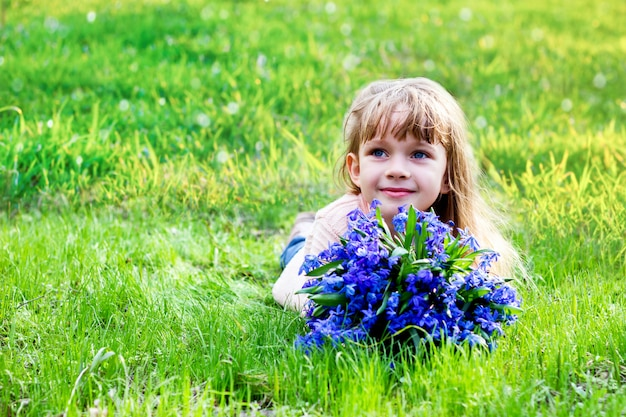 Girl with a bouquet of spring flowers on the green grass