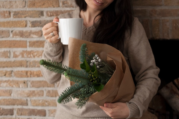 Girl with a bouquet of twigs in hands, in brown paper. near the brick wall. with a mug of coffee in hands