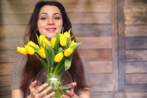 Girl with a bouquet of yellow tulips. girl with a gift of flowers in a vase. a gift for girls on a female holiday with yellow tulips on floor.