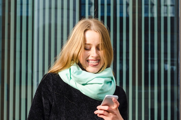 Girl with braces happily looks at phone and smiles. ginger woman with smile reads message, receives good news.