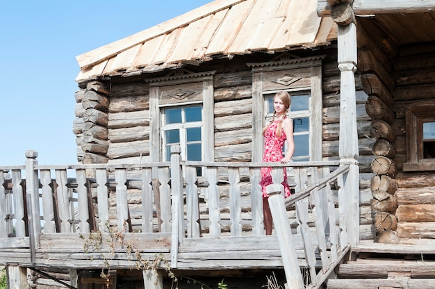 Girl with braids on the porch of an old wooden house