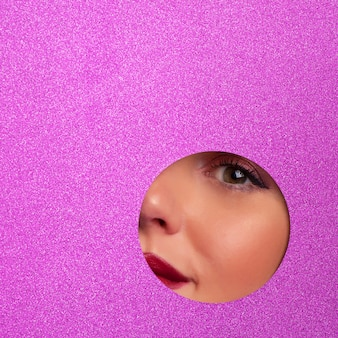 Girl with bright eyes make up looks through hole in violet paper