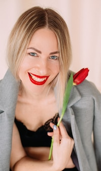Girl with bright lipstick holding a tulip
