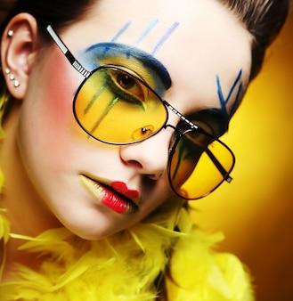 黄色の背景に明るいメイクアップを持つ少女をクローズアップ