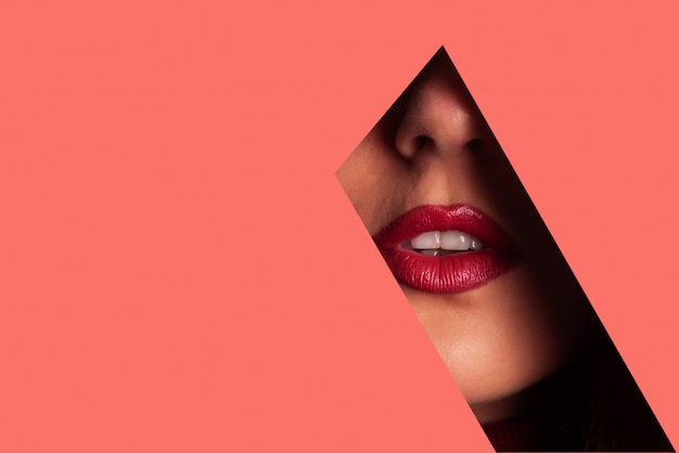 Girl with bright make up, red lipstick looking through hole in living coral paper