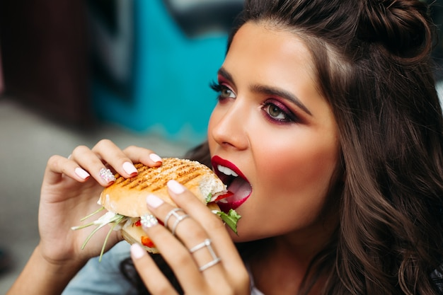 Girl with bright make-up taking a bite of burger.