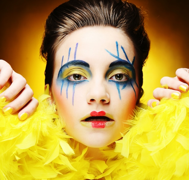 Girl with bright make up over yellow background, close up