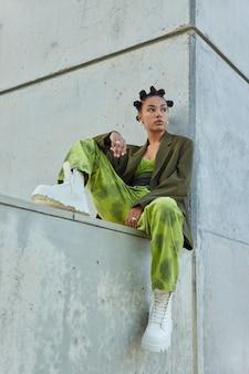 녹색 유행 옷을 입고 밝은 화장을 한 소녀 흰색 부츠는 회색 벽에 포즈를 취하고 도시 장소에서 신중하게 시간을 보냅니다.