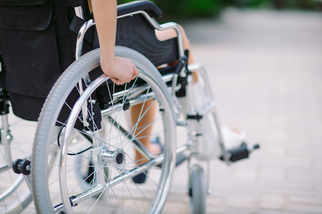 Girl with a broken leg sits in a wheelchair