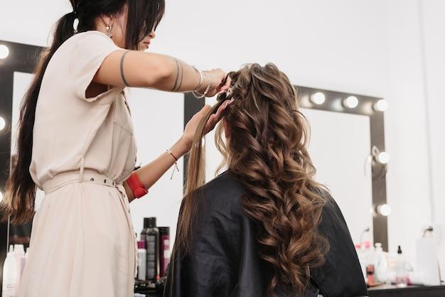 Девушка с каштановыми длинными вьющимися волосами в салоне красоты. утренняя подготовка невесты к дню свадьбы