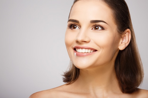 Girl with brown hair, clean fresh skin and naked shoulders posing at gray  wall, a model with light nude make-up, perfect teeth, shining smile.
