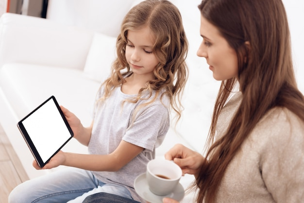 Girl with brown hair mother choose hairstyle on tablet.