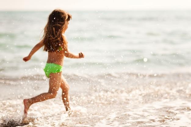 갈색 머리 소녀는 해변을 따라 실행